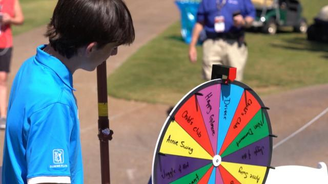 Wheel of Fore-tune with players and caddies at Shriners